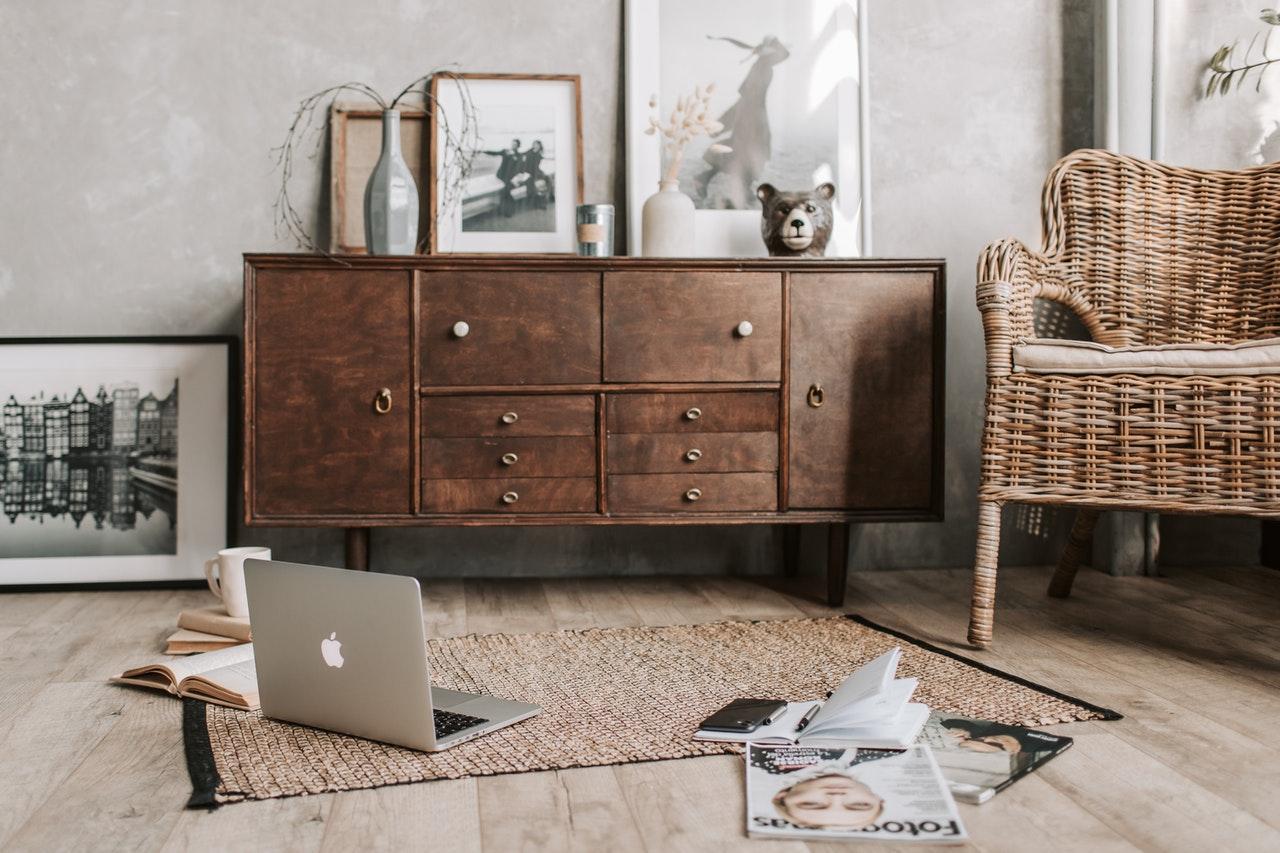 dark drown mid century modern furniture with wicker chair and macbook