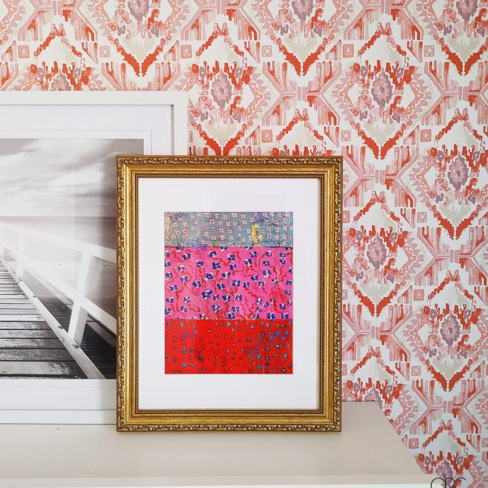 Gold frame with anthropologie print via Artfully walls. The art is red, blue, and pink with blue and white flowers on a coral ikat wallpaper