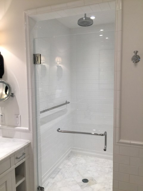 The all white bathroom with a grab bar in the shower