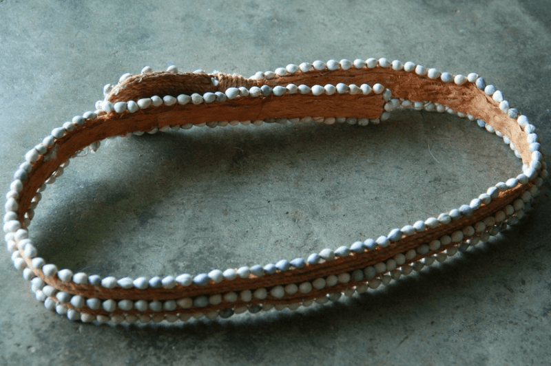 Clad in a belt with the fruit of the ipuh tree as a bead