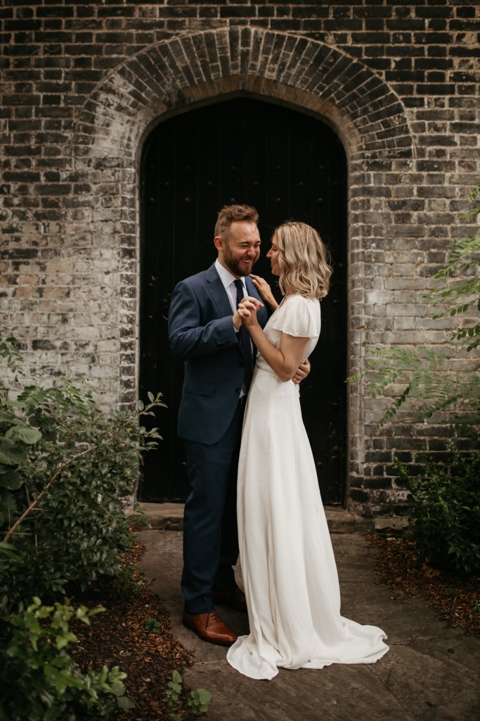 Bride wearing Vintage Silk Wedding Dress couple shoot moment in a brick alcove in London