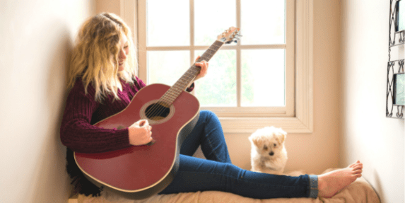 woman playing guitar with a white poodle