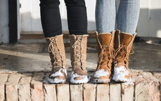 Two pairs of snow boots with snow covering the bottoms.