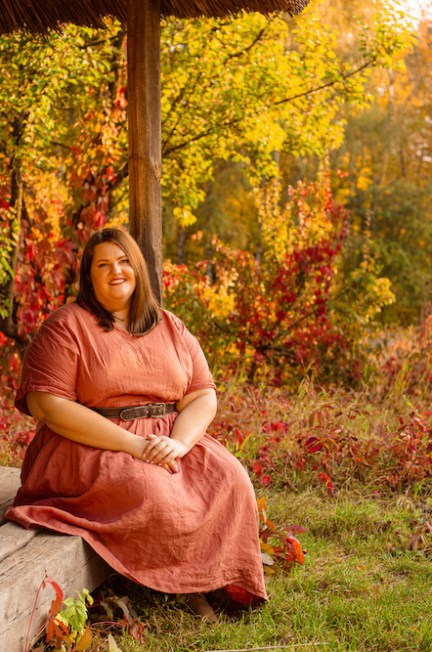 Beautiful and confident plus size model in red dress and brown boots posing outdoors at autumn landscape with traditional russian architecture