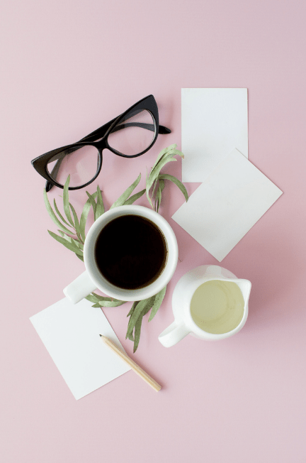 A collection of writing tools, glasses and coffee accessories on a pink table.