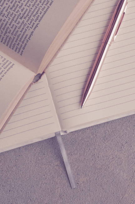 The edge of a book with a blank notebook underneath and a pink pen sitting on top