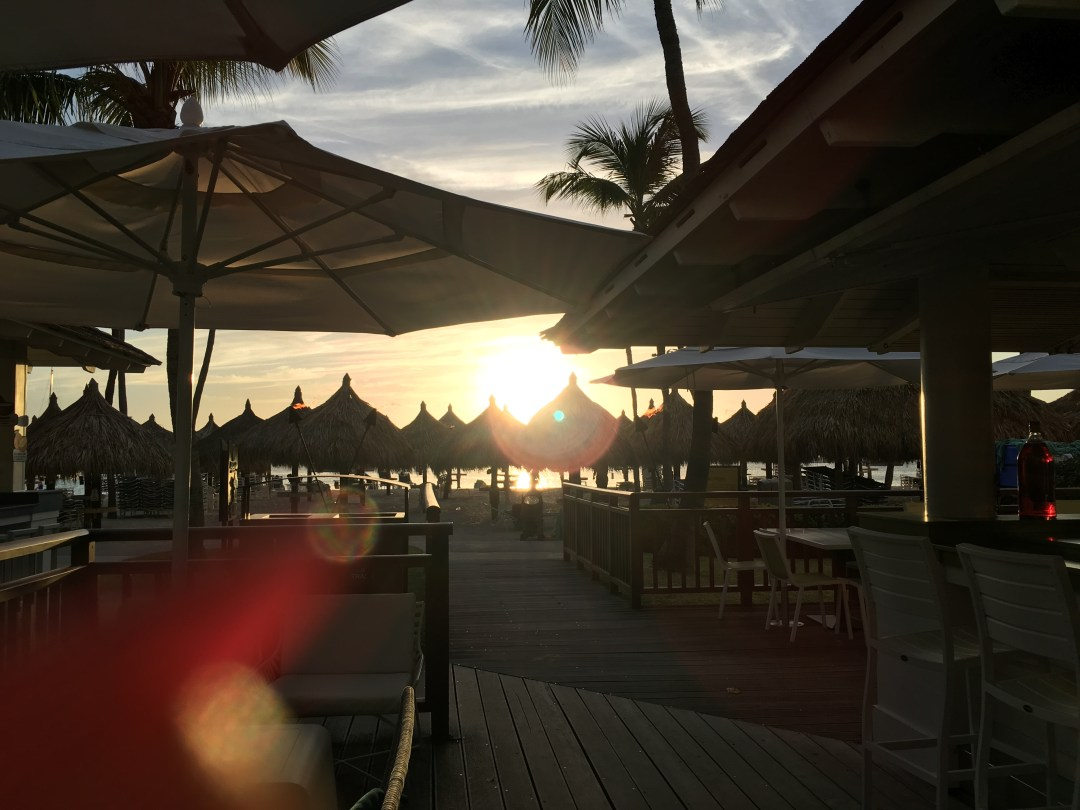 Watch the sunset at the Palms Beach Bar