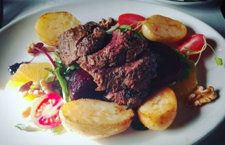 Balsamic and Lemon-marinated slices of Ostrich fillet served on a potato, beetroot, walnut and watercress salad.