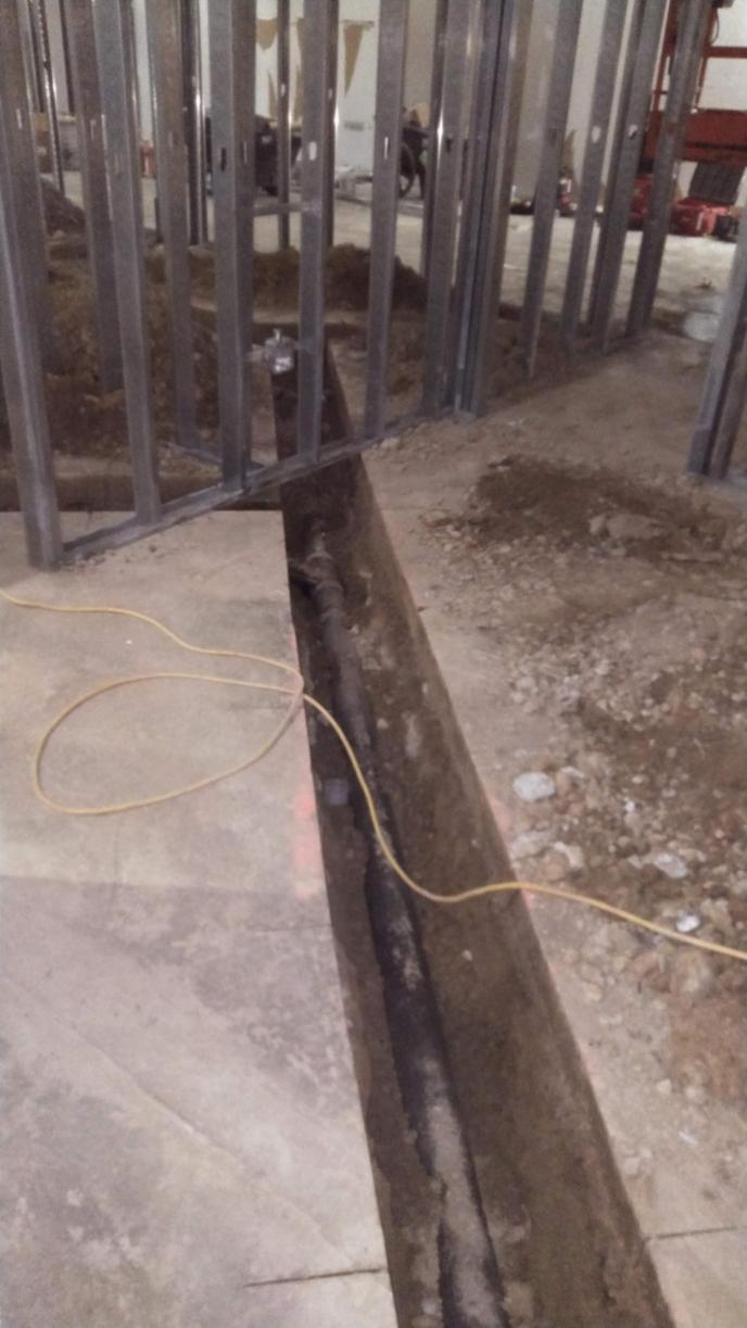 commercial sewer concrete floor cut and 4 inch no hub cast iron in ditch with steel stud walls on top of concrete