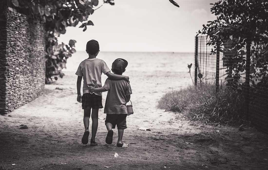 two kids walking arm in arm