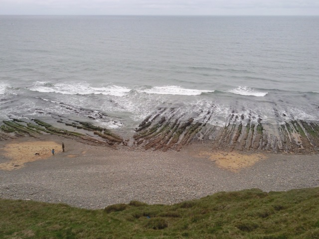 Beach with parallel rows of jagged rocks formed from rock vertically aligned strata