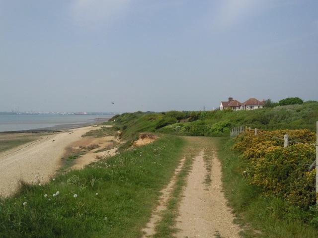 A sandy path on a low cliff above a sandy beach