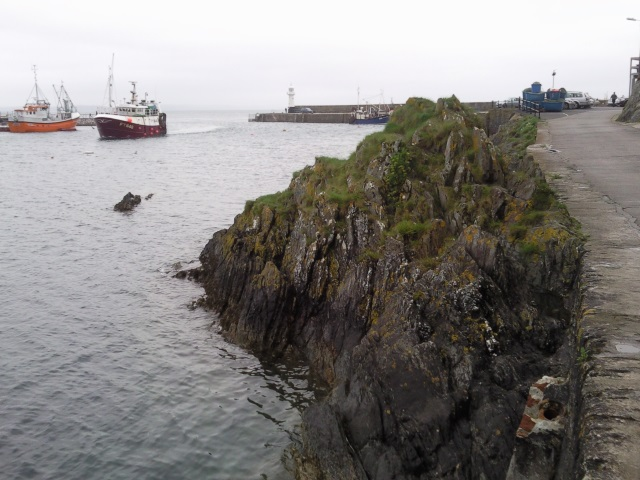 Mevagissey harbour with some jagged rocks visible within