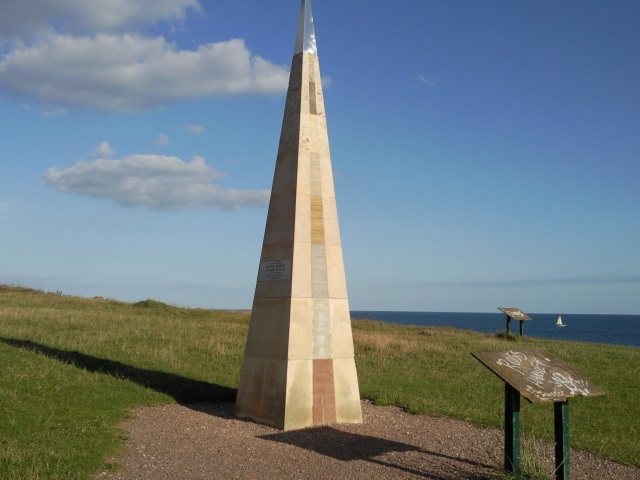 A tall, pyramidal obelisk of various types of stone. In front of it stands an information board from which the actual information has long since vanished.