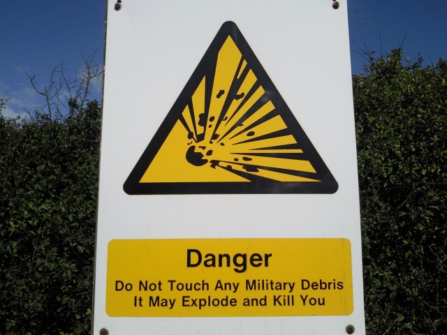 Sign: Danger. Do Not Touch Any Military Debris. It May Explode and Kill You.