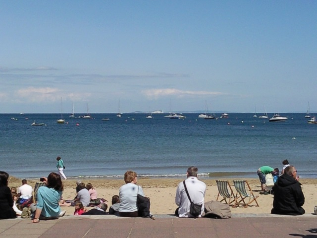 Looking out to sea from a busy beach in Swanage. The Isle of Wight sits on the horizon.