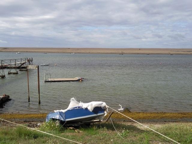 A boat on a beach facing the Fleet, a linear lagoon between the shore and a shingle bank