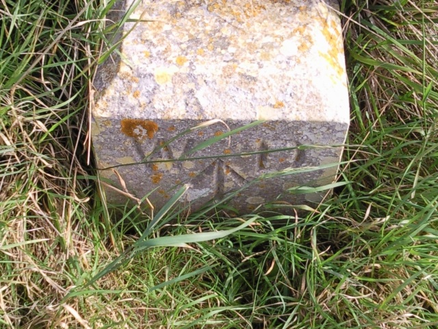 """An old War Department marker stone, engraved with """"WD"""" and the government broad arrow"""
