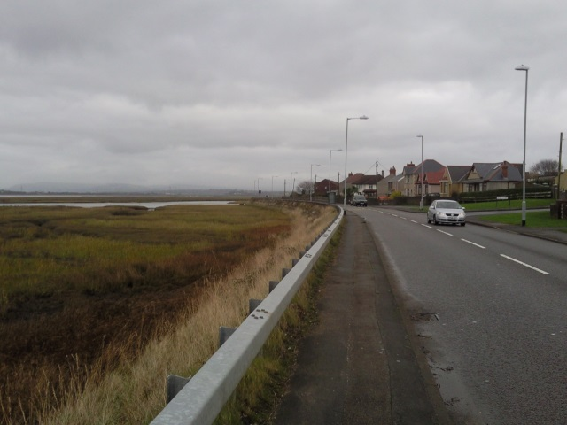 Penclawdd Promenade: an ordinary road and pavement, separated from the marsh by a crash barrier