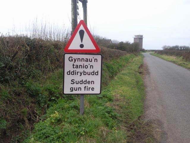 Warning sign: Gynnau'n tanio'n ddirybudd / Sudden gun fire