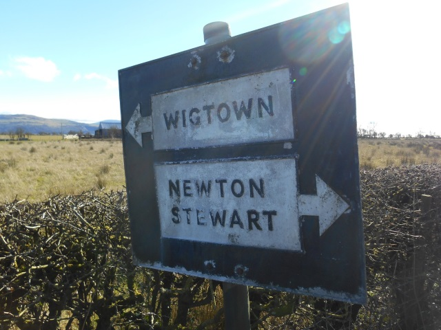 Pre-Worboys road sign pointing to Wigtown and Newton Stewart