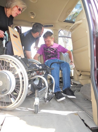 Photo of Patrick Ivison being assisted by two people within his van that is built for his needs.