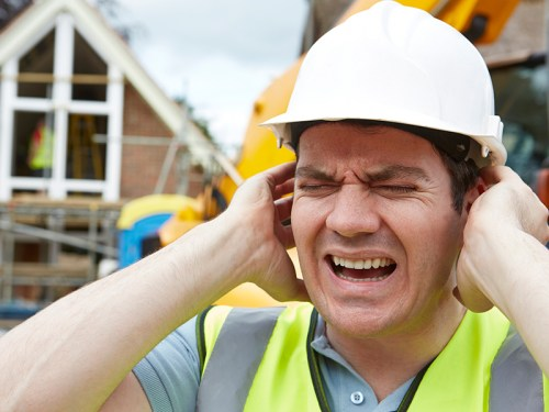 Picture of construction worker with hands over ears