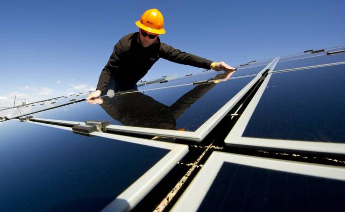 mies asentaa aurinkopaneelia