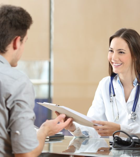 Happy doctor female wearing coat attending to her patient in a consultation while is holding a medical history sitting in a desktop