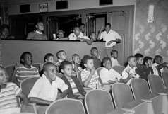 Children seated and standing in unidentified theater, circa 1950. Paul Henderson, HEN.00.B1-023.