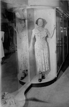Unidentified woman modeling dress inside store, circa 1949. Paul Henderson, HEN.00.B1-100.