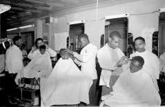 Interior of barbershop with customers and barbers, circa 1949. Paul Henderson, HEN.00.B1-104.