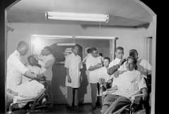 Interior of barbershop with customers and barbers, circa 1949. Paul Henderson, HEN.00.B1-108.