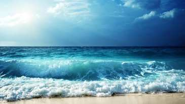 Seashore With Waves And Sunlight Reflecting On Water. .