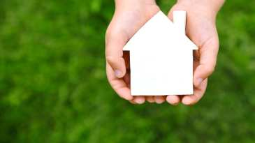 Two Hands Holding A Figure Of A House With A Green Background.