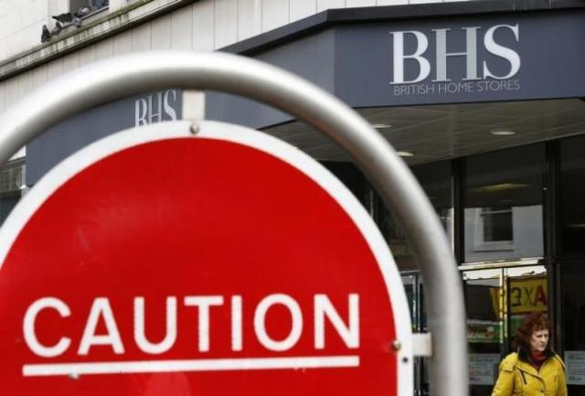 A woman walks past a BHS store in Leicester