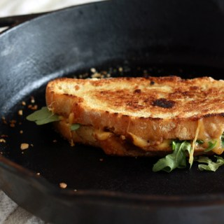 Grilled cheese sandwich with tomato-onion jam and arugula
