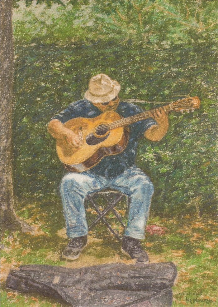 Busker playing an acoustic guitar at Loch Lomond Shores.