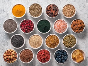 Various superfoods in bowl on gray background