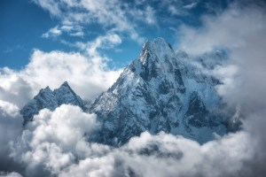 Manaslu mountain with snowy peak in clouds in sunny bright day