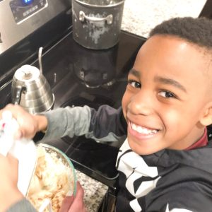 kid mixing up cheesecake mixture with a hand help mixer