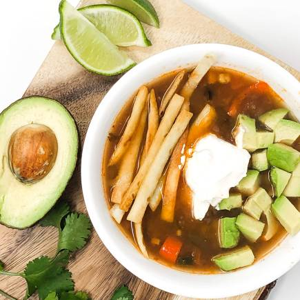 Vegetarian tortilla soup with fried tortilla stips, sour cream, and avocado. In a white bowl on a cutting board with lime and avocado.