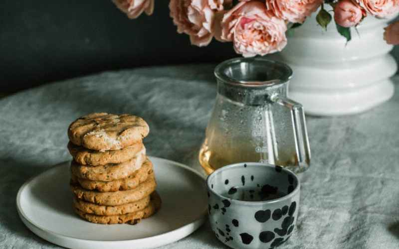 plate of cookies near vase of flowers