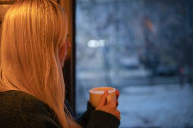 woman drinking coffee staring out window