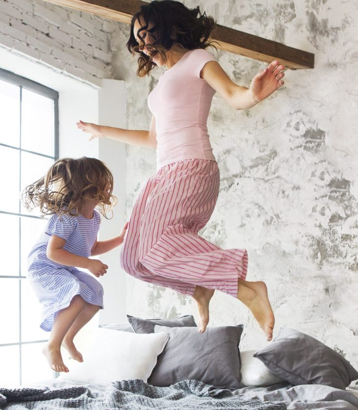mother and daughter jumping on bed