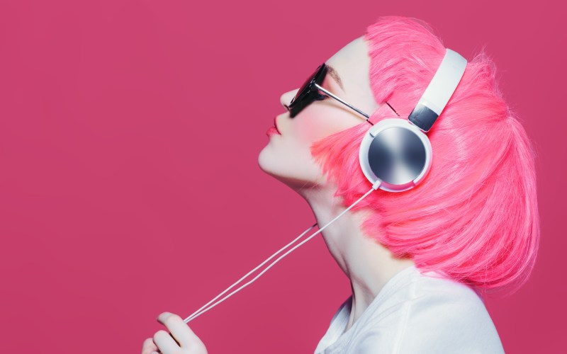 girl with pink hair listening to music