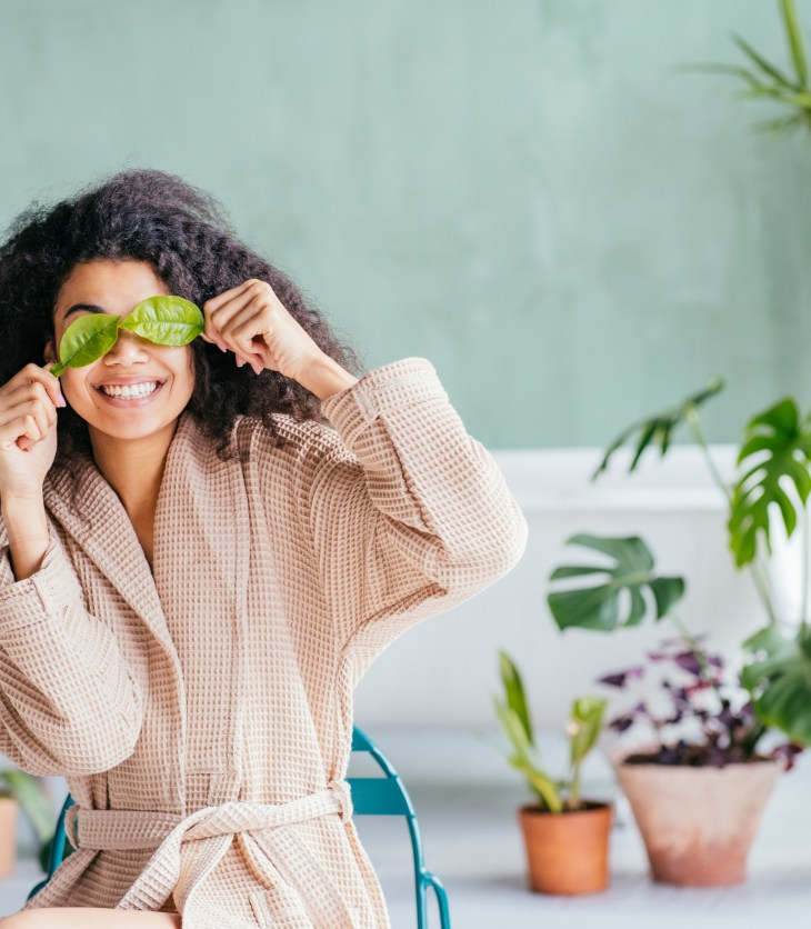 woman placing cucumbers of her eyes