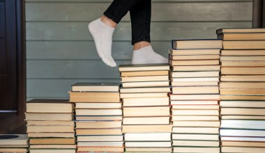 woman walking up stack of books