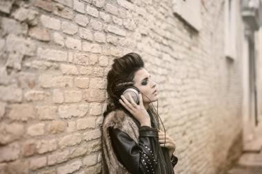 woman leaning against wall listening to music