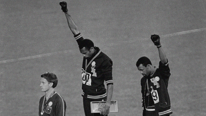 Gold medalist Tommie Smith (center) and bronze medalist John Carlos (right) showing the raised fist on the podium after the 200 m race at the 1968 Summer Olympics.